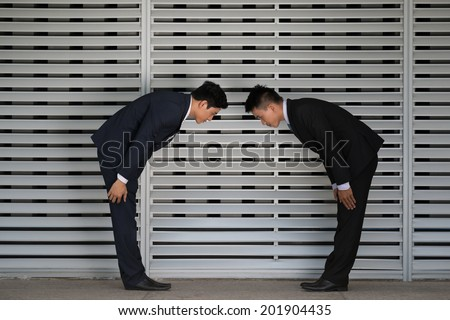 Vietnamese business partners making a low bow, side view - stock photo