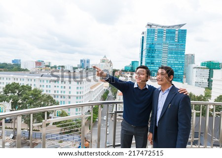 Vietnamese businessman pointing at something to his colleague while they are standing on the roof of the building - stock photo