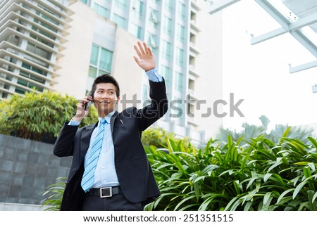 Vietnamese businessman waving his hand and talking on the phone - stock photo