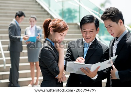 Vietnamese businesspeople having meeting outdoors - stock photo