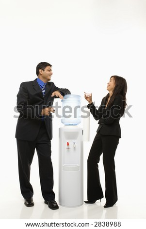 Vietnamese businesswoman and Indian businessman conversing at water cooler. - stock photo