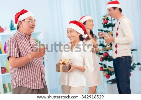 Vietnamese couple in Santa hats chatting at Christmas party - stock photo