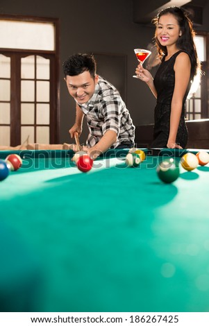 Vietnamese couple playing billiard in the pub - stock photo