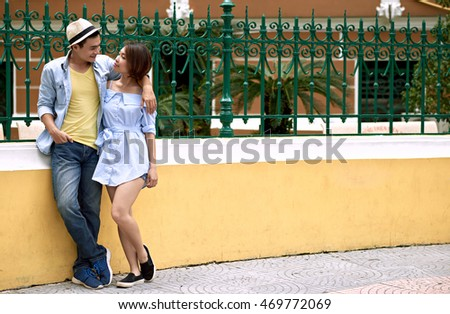 Vietnamese couple standing in the street and talking