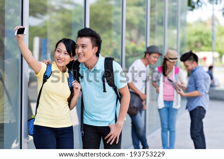 Vietnamese couple taking a selfie, while their friends using digital tablet - stock photo