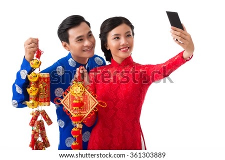 Vietnamese couple taking selfie with Tet decorations - stock photo