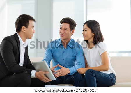 Vietnamese couple talking to advisor in the office