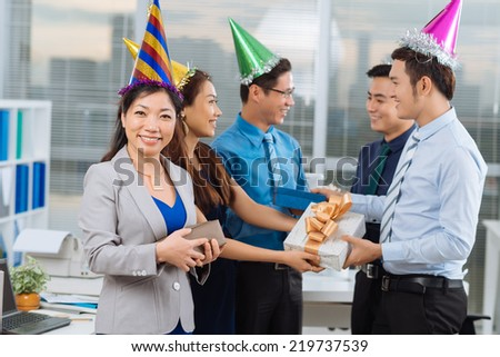 Vietnamese coworker exchanging presents at the office party - stock photo