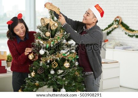 Vietnamese coworkers decorating Christmas tree in office