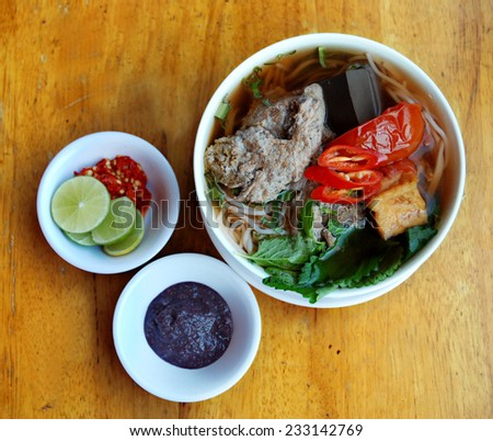 Vietnamese crab noodle soup (Bun rieu), Vietnamese Cuisine. A meal cooked with pork stock, broth (made by crab mixture and pork/chicken stock, dried shrimp), tomatoes, light fried tofu, shrimp paste.  - stock photo