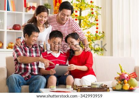 Vietnamese family gathered around tablet computer at tet celebration - stock photo