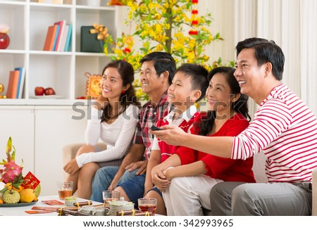 Vietnamese family watching tv at the celebration of Tet - stock photo