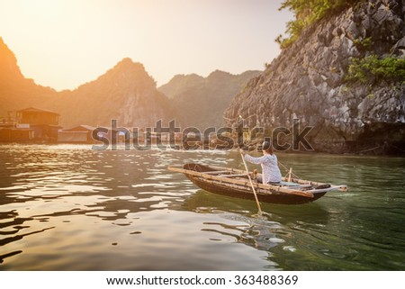 Vietnamese female in traditional boat returns to floating fishing village in the Halong Bay at sunset. The Gulf of Tonkin, the South China Sea, Vietnam. Karst towers-isles are visible in background. - stock photo