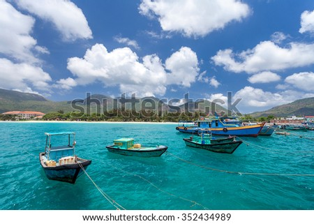 Vietnamese fishing boats on a tropical Con Dao Island. View from the pier in the direction of a beach with white sand. - stock photo