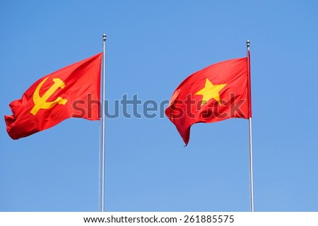 Vietnamese Flag and Communist Party of Vietnam flag in the Wind, Against Blue Skies - stock photo
