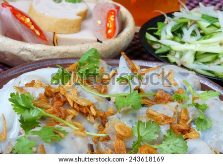 Vietnamese food, Banh Cuon name Rice noodle roll or rolled cake, is made from rice batter filled with mushroom, pork, served with Vietnam pork sausage, sliced cucumber,  bean sprouts and sauce  - stock photo