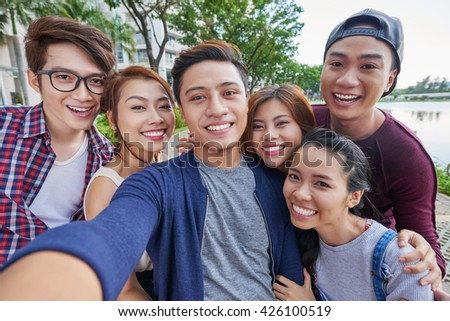 Vietnamese friends taking selfie together outdoors