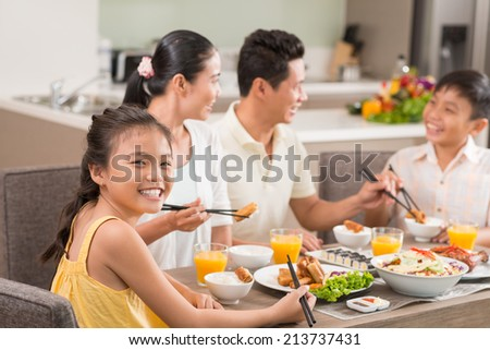 Vietnamese girl enjoying national food at the family dinner table - stock photo