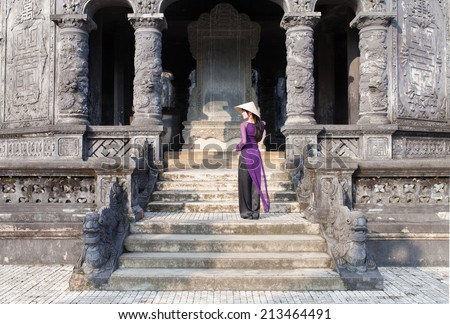 Vietnamese girl in long purple dress (ao dai ) anda conical hat is siting at king tomb of king Tu Duc at old capital Hue, Vietnam . Tomb of Tu Duc is one of most famous place and largest king's tomb - stock photo