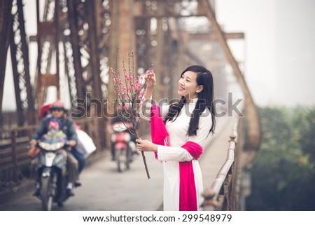 Vietnamese girl on Long Bien bridge in Hanoi, Vietnam. Long Bien bridge is a historic cantilever bridge across the Red River in Hanoi city. - stock photo