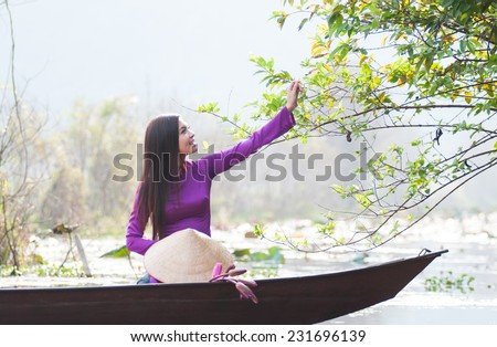 Vietnamese girl with traditional dress (ao dai) and conical hat in Yen stream in Hanoi, Vietnam