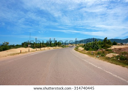 Vietnamese highway, cross sand hill, jungle, countryside or mountain, route for travel, discovery Vietanam, landscape of rural under blue sky on day - stock photo