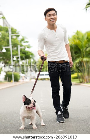 Vietnamese man walking his French bulldog - stock photo