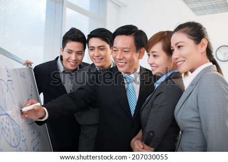 Vietnamese manager explaining business strategy to the coworkers - stock photo