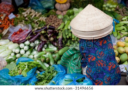Vietnamese market vendor selling vegetables - stock photo