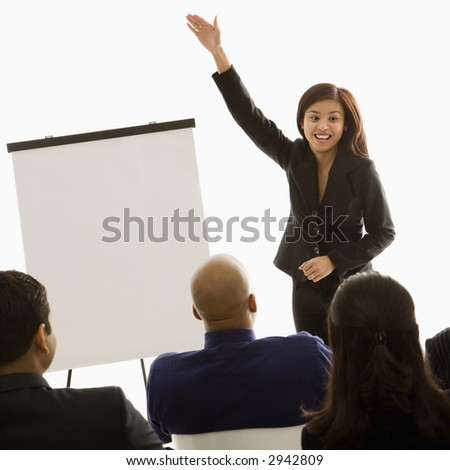 Vietnamese mid-adult woman standing in front of business group gesturing for a presentation.