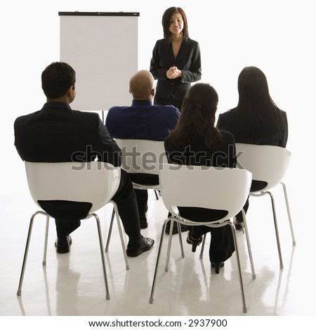 Vietnamese mid-adult woman standing in front of business group leading presentation.