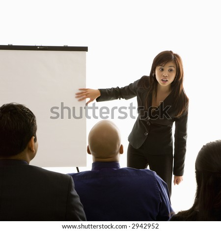 Vietnamese mid-adult woman standing in front of business group pointing to presentation. - stock photo