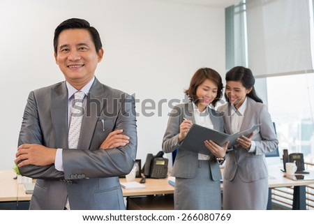 Vietnamese middle-aged businessman with his female colleagues in background