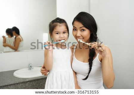 Vietnamese mother and daughter brushing teeth together - stock photo