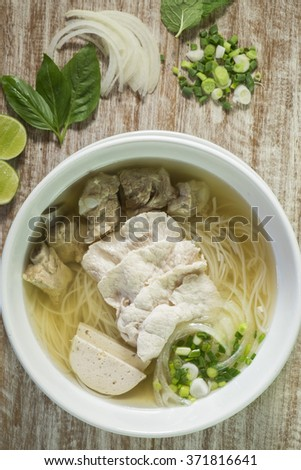 Vietnamese noodle, pho, with ingredients on wooden background - stock photo
