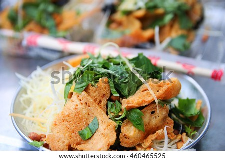 Vietnamese Papaya delight salad: Sliced papaya, dried beef, herb and spice mixed salad, popular street food in Saigon, Vietnam - stock photo