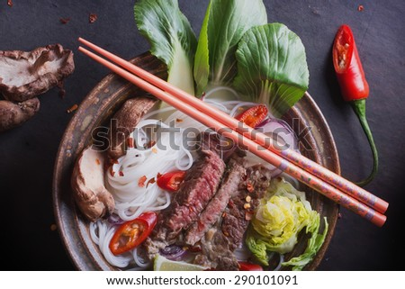 Vietnamese Pho Bo soup served in vintage oriental bowl with chop sticks, seasoning and greens on background