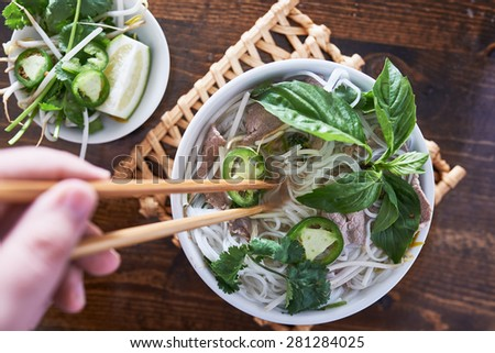 vietnamese pho with beef being eaten with chopsticks - stock photo