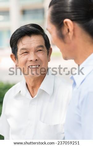 Vietnamese senior man talking to his son - stock photo