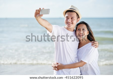 Vietnamese smiling young couple taking selfie together