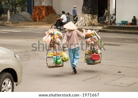 Vietnamese street vendor in Ho Chi Minh City (Saigon) carrying their goods across a street - stock photo