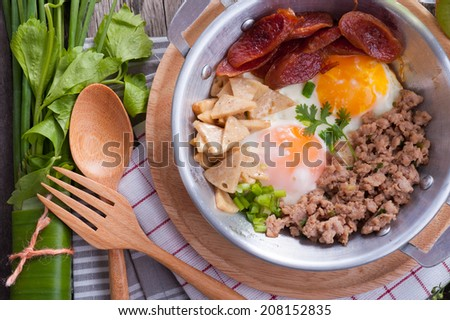 Vietnamese style fried egg in pan with white pork sausage, Chinese sausage, and pork on wood table. - stock photo