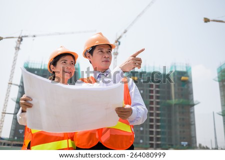Vietnamese supervisors in hardhats inspecting construction site - stock photo