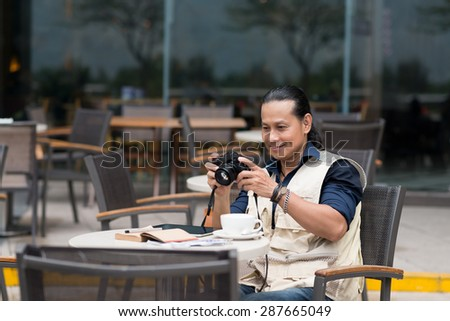 Vietnamese tourist sitting in outdoor cafe and watching pictures on his digital camera