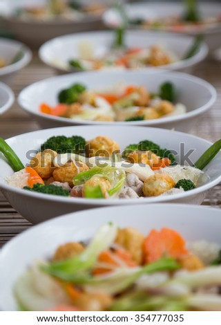 Vietnamese traditional bowl of mixed food including fried egg, fork, onion, cauliflower, carrot, and soup. Center focus.
