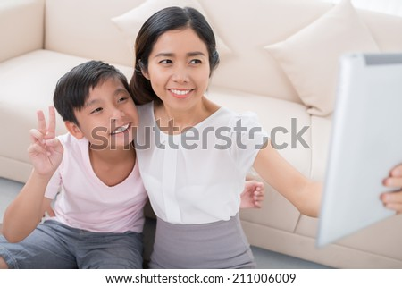 Vietnamese woman and her son taking selfie with digital tablet - stock photo