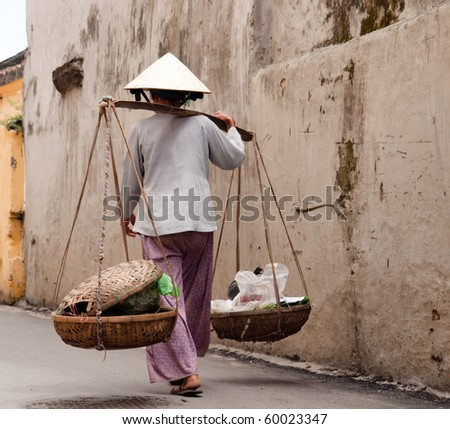 Vietnamese woman in a narrow street - stock photo