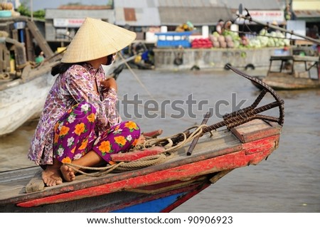Vietnamese Woman on a Boat at a Morning Floating Market in the Mekong Delta. - stock photo