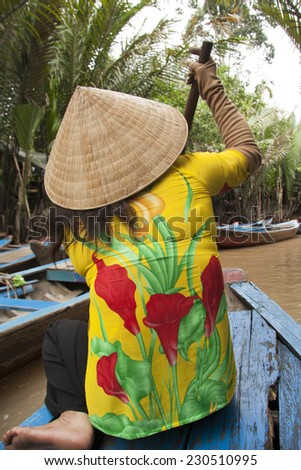 Vietnamese woman paddles a boat in Mekong River in Vietnam - stock photo
