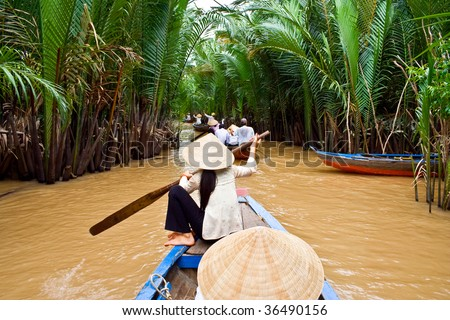 Vietnamese woman rowing a boat in Mekong River in Vietnam